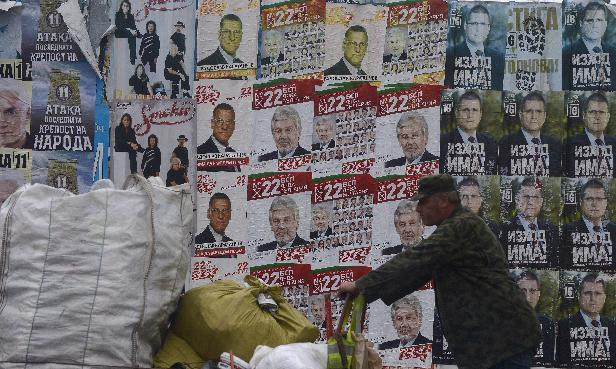 A man pushes a cart in front of election posters for Bulgarian Socialist Party candidate Stefan Danaliov on October 3, 2014 (AFP Photo/Nikolay Doychinov)