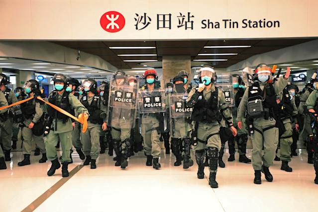 Riot police enter the shopping mall to disperse the protesters during Labor Day in Hong Kong, Friday, May 1, 2020 amid the coronavirus COVID-19 pandemic. Hong Kong police deployed pepper spray during a protest in a Hong Kong shopping mall on Friday, as they dispersed over a hundred protesters who gathered to sing and chant pro-democracy slogans.