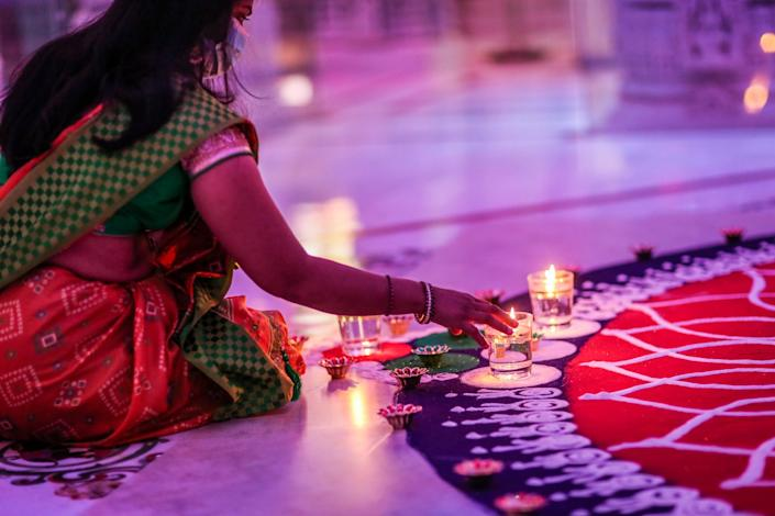 A woman kneels and places a candle on the edge of an intricate work of sand art inside a Hindu temple