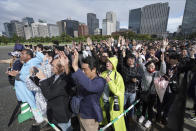 """People outside of the Tokyo Imperial Palace follow Prime Minister Shinzo Abe's three """"banzai"""" cheers for the 59-year-old Emperor Naruhito during the enthronement ceremony, Tuesday, Oct. 22, 2019, in Tokyo, Japan. (AP Photo/Eugene Hoshiko)"""