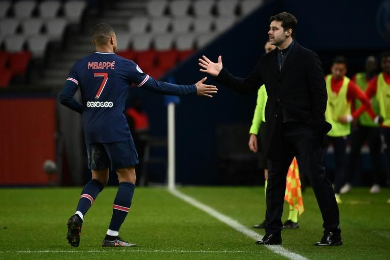 Kylian Mbappe (L) celebrates with PSG coach Mauricio Pochettino after scoring his 15th league goal of the season against Nimes