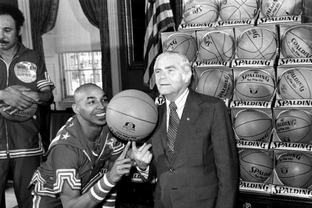 """FILE - In this Feb. 15, 1977, file photo, the Harlem Globetrotters' Fred """"Curly"""" Neal of shows New York City Mayor Abe Beame the art of balancing a basketball on a finger during ceremony at City Hall. Neal, the dribbling wizard who entertained millions with the Harlem Globetrotters for parts of three decades, has died the Globetrotters announced Thursday, March 26, 2020. He was 77. Neal played for the Globetrotters from 1963-85, appearing in more than 6,000 games in 97 countries for the exhibition team known for its combination of comedy and athleticism. (AP Photo/File)"""