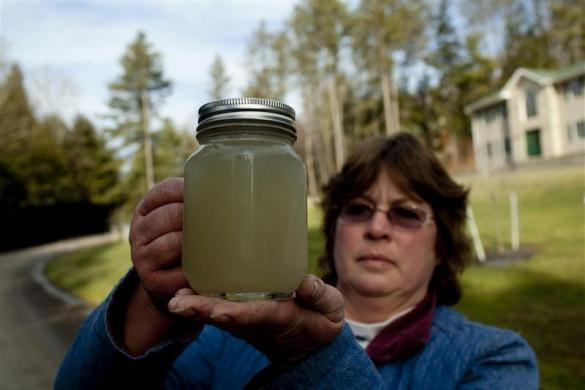 Carol French of the Pennsylvania Landowner Group for the Awareness and Solutions holds a jar of cloudy water from her well in rural Bradford County, Pennsylvania January 10, 2012.