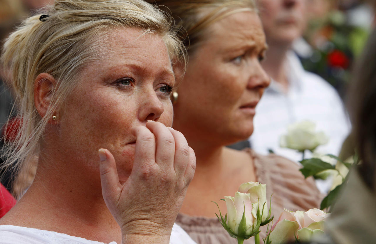A woman reacts during a vigil with thousands of others in memory of the eight people killed in Friday's blast in Oslo and the 68 who died in the shooting at the youth camp on Utoya, in Vik, near Sundvollen close to Utoya island, near Oslo, Norway, Tuesday, July 26, 2011. (AP Photo/Ferdinand Ostrop)