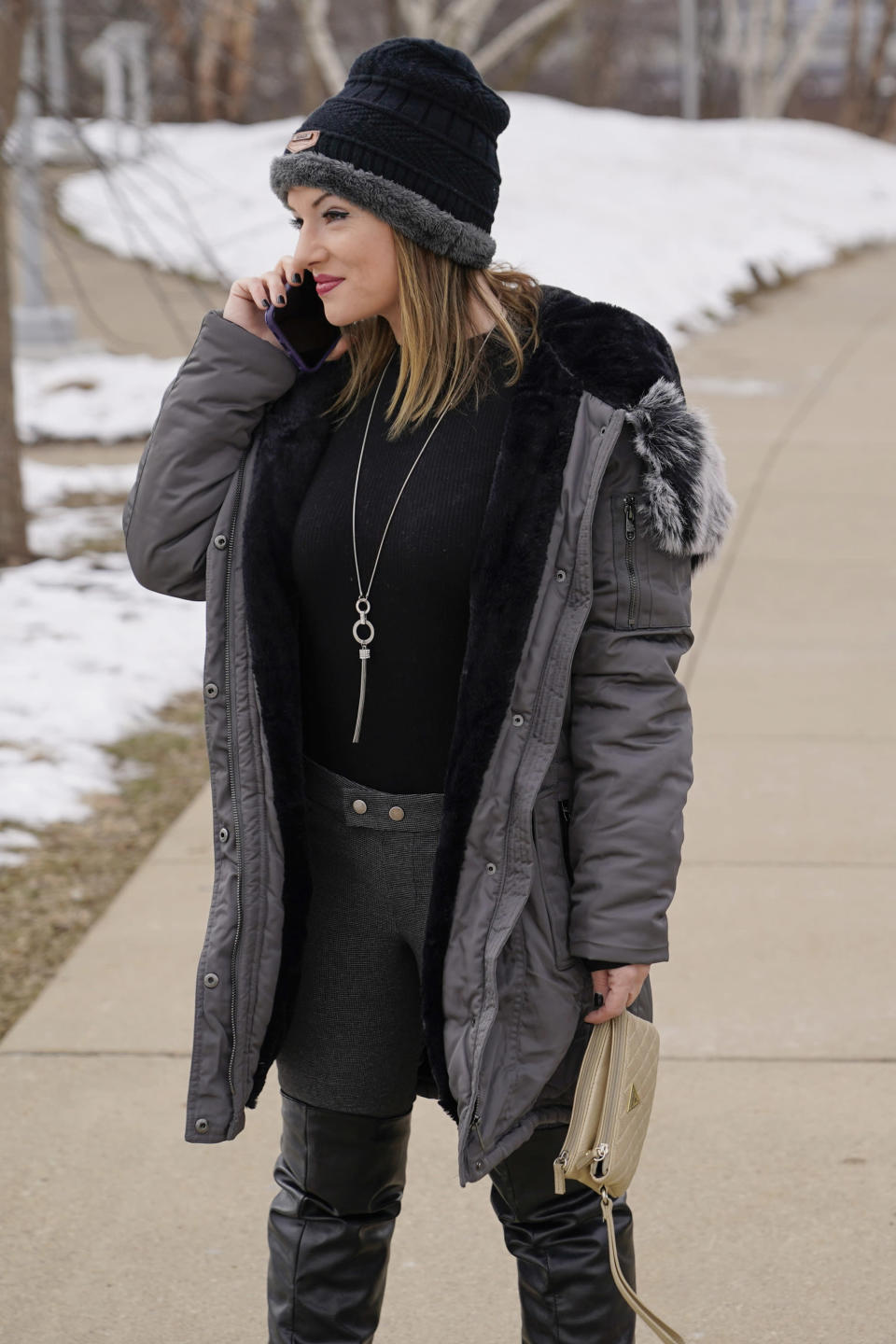 "In this Monday, Feb. 8, 2021, photo, Allissa Star talks on her phone as she walks near the north shore of the Allegheny River in Pittsburgh. Starr worked about a week every month at a brothel in Pahrump, Nev., outside of Las Vegas. Then the pandemic led to the shuttering of Nevada's licensed bordellos, the only place where prostitution is legal in the state, and they have remained closed since March, leaving sex workers like Starr struggling to pay the bills and turning to alternatives like ""virtual"" dates. (AP Photo/Keith Srakocic)"
