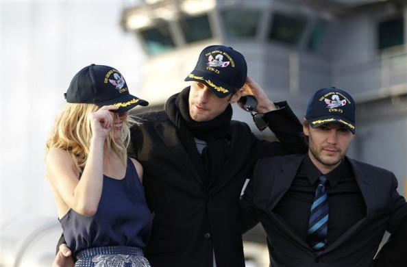 "Cast members of the film ""Battleship"", (from L-R) Brooklyn Decker, Alexander Skarsgard, and Taylor Kitsch wear caps during a news conferenc atop a flight deck of aircraft carrier USS George Washington at Yokosuka port, south of Tokyo April 2, 2012."