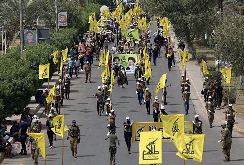 "FILE - In this June 8, 2018 file photo, Iraqi Popular Mobilization Forces march as they hold their flag and posters of Iraqi and Iranian Shiites spiritual leaders during ""al-Quds"" or Jerusalem Day, in Baghdad, Iraq. When U.S. Secretary of State Mike Pompeo sat down with Iraqi officials in Baghdad earlier this month as tensions were mounting between the U.S. and Iran, he delivered a nuanced message: If you're not going to stand with us, stand aside. (AP Photo/Hadi Mizban, File)"