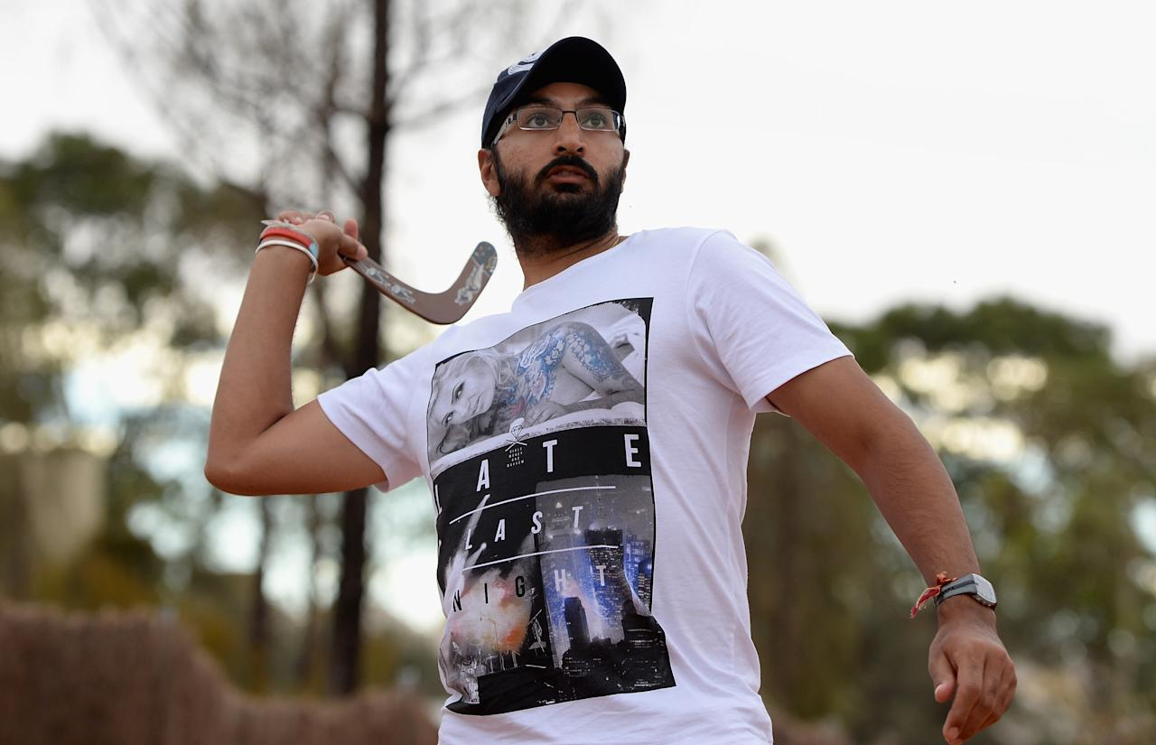 AYERS ROCK, AUSTRALIA - NOVEMBER 26:  Monty Panesar of England throws a boomerang during a team visit to Uluru, which is also known as Ayers Rock, on November 26, 2013 in Ayers Rock, Australia.  (Photo by Gareth Copley/Getty Images)