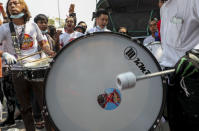An anti-coup protester beats a drum with a defaced image of Commander-in-Chief Senior Gen. Min Aung Hlaing during a street march in Mandalay, Myanmar, Thursday, Feb. 25, 2021. Social media giant Facebook announced Thursday it was banning all accounts linked to Myanmar's military as well as ads from military-controlled companies in the wake of the army's seizure of power on Feb. 1. (AP Photo)