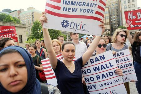 FILE PHOTO - Protesters hold signs against U.S. President Donald Trump's limited travel ban in New York City, U.S. on June 29, 2017. REUTERS/Joe Penney/File Photo