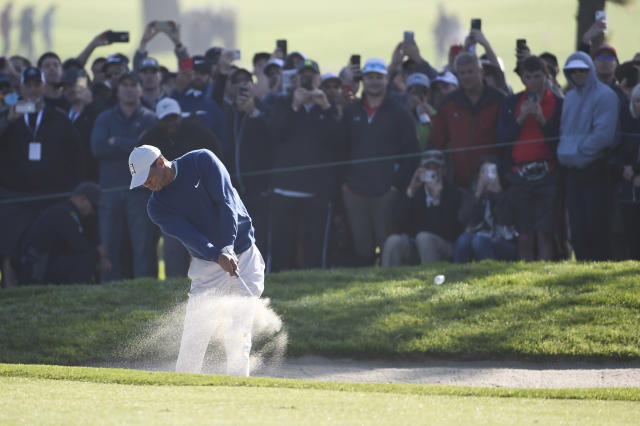 Tiger Woods hits out of the bunker on the first hole of the South Course at Torrey Pines Golf Course during the third round of the Farmers Insurance golf tournament Saturday Jan. 25, 2020, in San Diego. (AP Photo/Denis Poroy)