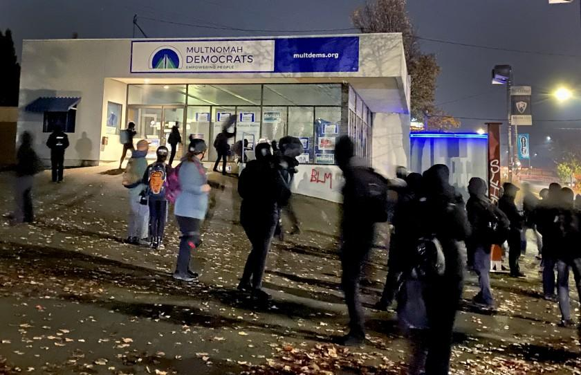 "Activists, at rear, break windows Sunday night, Nov. 8, 2020, at the county Democratic Party headquarters in Portland, Ore., after spray-painting ""BLM"" and an anti-Joe Biden slogan on walls. Black community leaders say the activists have hijacked the protest movement, undermining Black Lives Matter causes. Photo by Brenda Griswold for the Times"