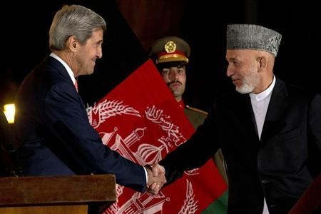 Afghanistan's President Hamid Karzai shakes hands with U.S. Secretary of State John Kerry after a news conference at the Presidential Palace in Kabul