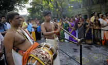 FILE- In this Jan. 15, 2019 file photo, Sri Lankan ethnic Tamil Hindu devotees pray as musicians play traditional instruments Nadaswaram, center and thavil, left, during harvest festival 'Thai Pongal' at a Hindu temple in Colombo, Sri Lanka. A proposed amendment to Sri Lanka's constitution that will consolidate powers in the President's hands has raised concerns about the independence of the country's institutions and the impact on its ethnic minorities who fear their rights could be undermined by the majoritarian will. (AP Photo/Eranga Jayawardena, File)