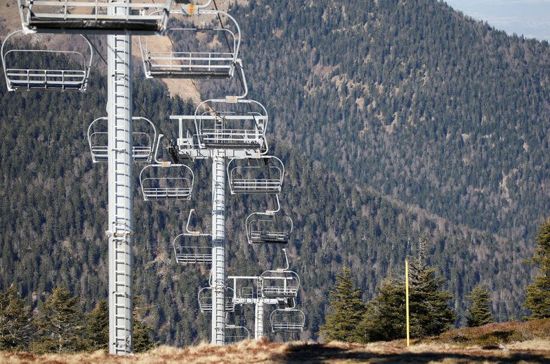 Chairlifts are pictured over ski slopes closed due to lack of snow, at the ski resort of The Mourtis in Boutx