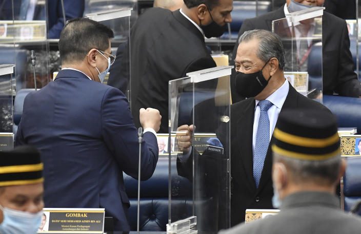 In this photo release by Malaysia Information Ministry, Malaysia's Prime Minister Muhyiddin Yassin, right, fist-bumps with Minister of International Trade and Industry Azmin Ali after the budget 2021 vote during a session of the lower house of parliament, in Kuala Lumpur, Malaysia Thursday, Nov. 26, 2020. Malaysia's Parliament Thursday approved the government's proposed 2021 budget, throwing a political lifeline to embattled Prime Minister Muhyiddin Yassin amid strong resistance to his nine-month-old leadership. (Famer Roheni/Malaysia's Department of Information via AP)