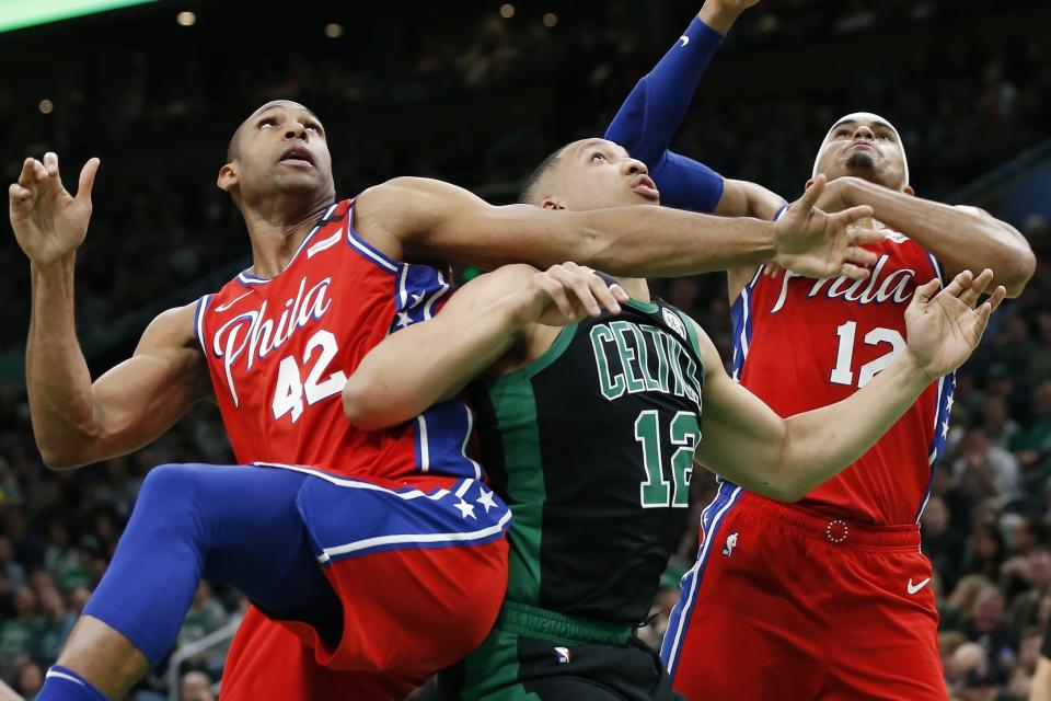 Boston Celtics' Grant Williams, center, battles against Philadelphia 76ers' Al Horford (42) and Tobias Harris, right, for a rebound during the first half of an NBA basketball game in Boston, Saturday, Feb. 1, 2020. (AP Photo/Michael Dwyer)
