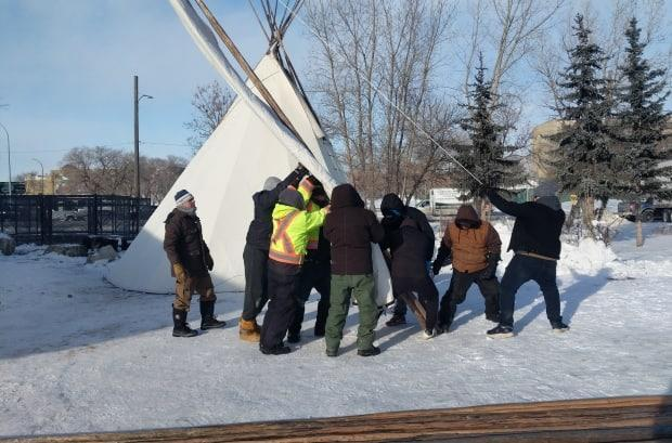 Volunteers from Winnipeg's Indigenous community help set up two teepees and a prospector tent for the homeless population near Thunderbird House on Tuesday.