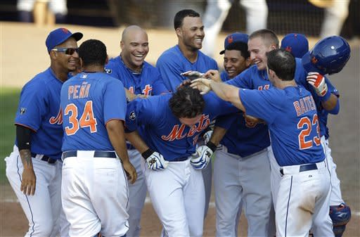 New York Mets' Ike Davis, center, is greeted by teammates at home plate after hitting a solo home run to end a spring training baseball game against the New York Yankees in Port St. Lucie, Fla., Tuesday, April 3, 2012. The Mets won 7-6. (AP Photo/Patrick Semansky)