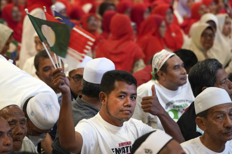A member from UMNO (United Malays National Organisation) waves PAS (Pan-Malaysian Islamic Party) parties flag during an event of officially join alliance in Kuala Lumpur, Malaysia, Saturday, Sept. 14, 2019. Two major opposition parties in Malaysia have forged a political alliance to consolidate support from the country's majority ethnic Malay Muslims, a move that could threaten Prime Minister Mahathir Mohamad's government in the next general elections. (AP Photo/Vincent Thian)
