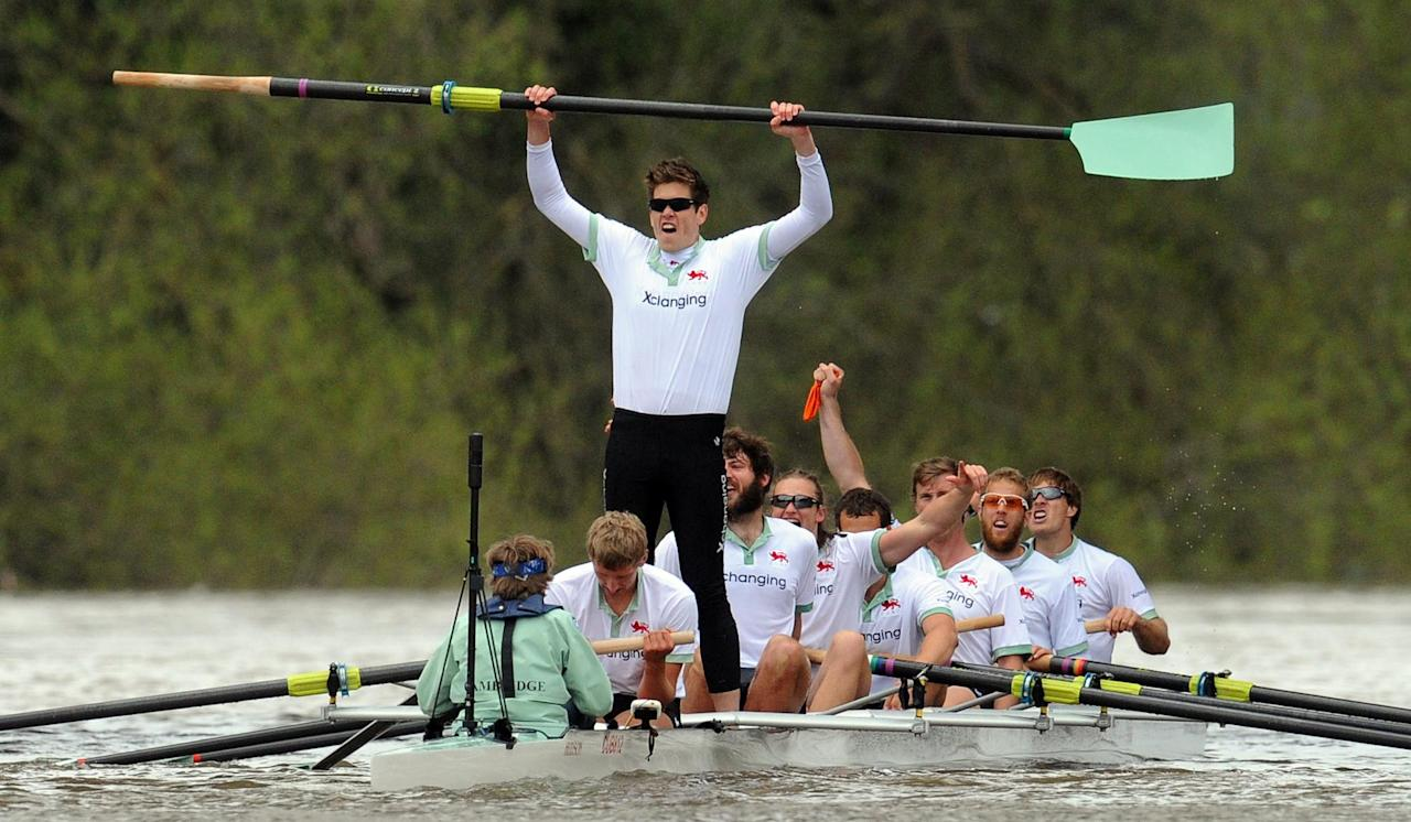Cambridge's Alexander Scharp, standing, celebrates victory over Oxford in the 158th Boat Race on the river Thames, London Saturday April 7, 2012. Cambridge won a dramatic Boat Race against Oxford on Saturday following a 31-minute mid-race postponement after a man jumped into the River Thames and swam between the crews. When the race was restarted halfway along the course, Oxford's German rower Dr. Hanno Wienhausen lost half of his oar after the crews clashed allowing Cambridge to cruise to victory up against effectively seven opponents. A margin of victory wasn't given by officials. (AP Photo/Anthony Devlin/PA) UNITED KINGDOM OUT