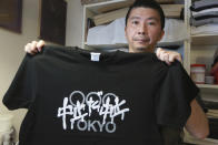 """Designer Susumu Kikutake shows anti-Olympics T-shirt during an interview with the Associated Press in Tokyo, Wednesday, June 9, 2021. An online article showcasing his design calling for the Olympics to be cancelled resulted in harsh online comments, and he sold only around 10 shirts a month before the pandemic. But demand for the t-shirts has boomed in the past two months, with sales reaching 100 shirts in April and 250 in May. The characters on the shirt read """"Cancelation, Cancelation"""". (AP Photo/Koji Sasahara)"""