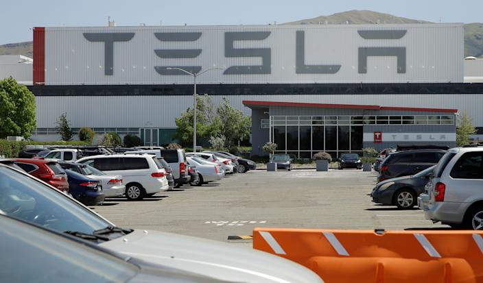 Vehicles are seen parked at the Tesla plant Monday, May 11, 2020, in Fremont, Calif. The parking lot was nearly full at Tesla's California electric car factory Monday, an indication that the company could be resuming production in defiance of an order from county health authorities.