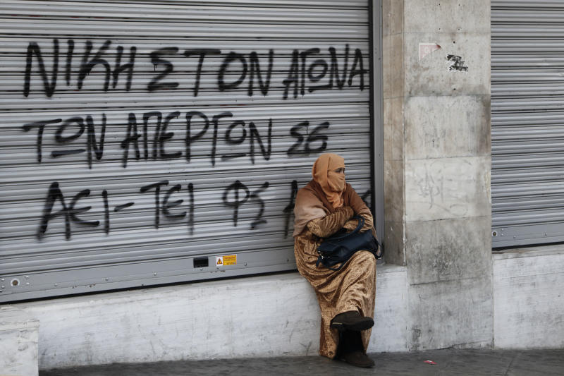 "A woman wearing a headscarf sits at the shuttered entrance of a bank on Athens' main Syntagma Square, in Greece's capital on Monday, Dec. 16, 2013. The graffiti on the shutters reads ""Victory for the Struggle at Universities and Polytechnics."" Athens University has been closed for 14 weeks due to a strike by administrative staff against personnel cuts imposed as part of Greece's bailout agreements. (AP Photo/Dimitri Messinis)"