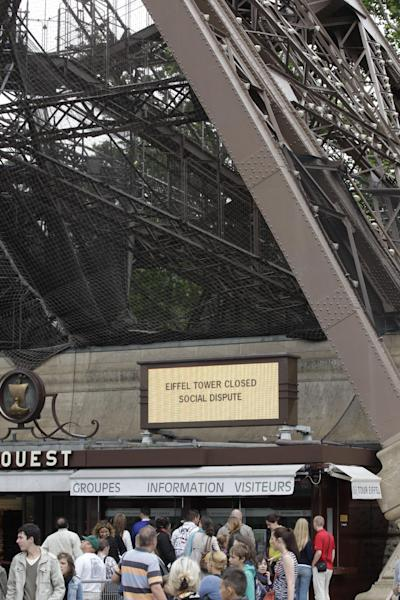 Visitors are gathered at the foot of the Eiffel Tower which is closed because of a strike, Tuesday June 25, 2013. The 124-year-old tower, normally open 365 days a year, sees about 25,000 tourists daily. It occasionally closes because of suicide threats, bomb threats or strikes.(AP Photo/Remy de la Mauviniere)