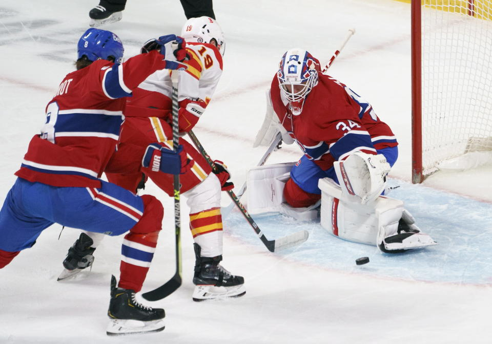 Montreal Canadiens goaltender Jake Allen makes a save on Calgary Flames' Matthew Tkachuk as Canadiens' Ben Chiarot defends during the first period of an NHL hockey game Friday, April 16, 2021, in Montreal. (Paul Chiasson/The Canadian Press via AP)