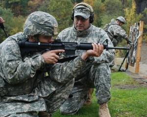 Soldier aiming rifle, with instructor next to him