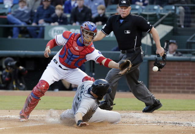 Seattle Mariners' Dustin Ackley (13) slides into home to score as Texas Rangers catcher Robinson Chirinos, left, reaches for the ball during the second inning of a baseball game on Wednesday, April 16, 2014, in Arlington, Texas. (AP Photo/Brandon Wade)
