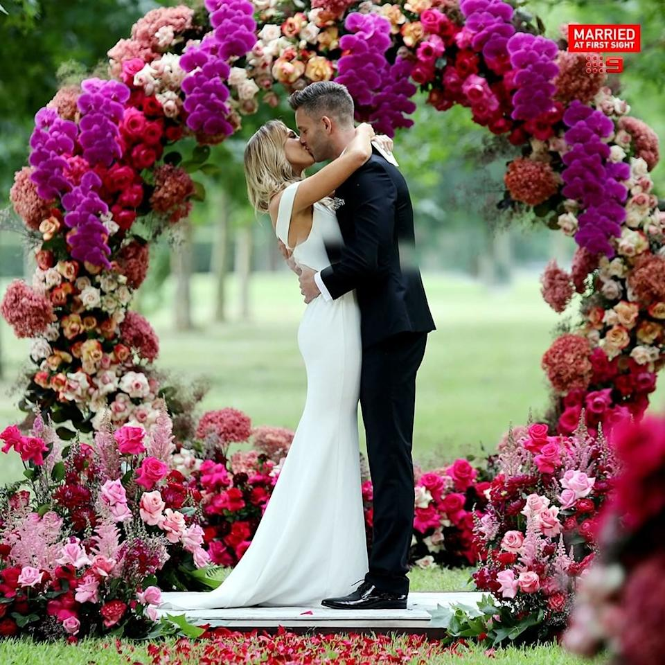 Jake and Bec on their MAFS wedding day under a flower arch