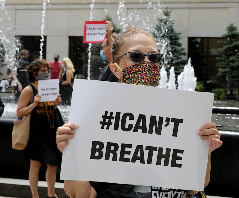 """Susan Sheppard holds an """"I can't breathe"""" sign during a vigil for George Floyd at the Renaissance Plaza in White Plains, New York, on Friday."""