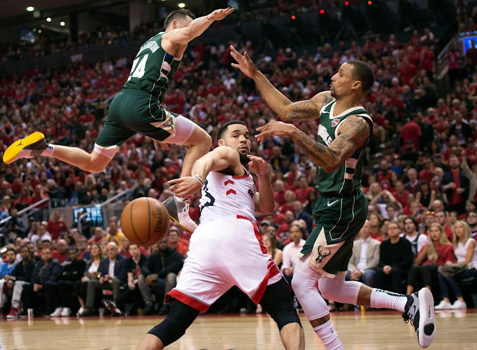 Toronto Raptors guard Fred VanVleet, center, passes the ball behind his back past Milwaukee Bucks guards Pat Connaughton (24) and George Hill, right, during the second half of Game 3 of the NBA basketball playoffs Eastern Conference finals in Toronto, Sunday, May 19, 2019. (Nathan Denette/The Canadian Press via AP)