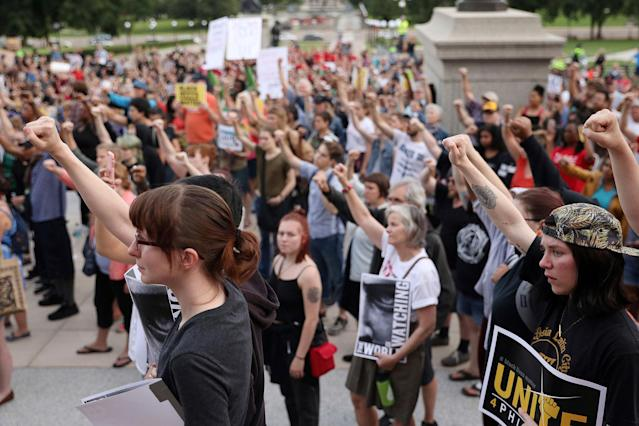 <p>Supporters of Philando Castile hold their fists up in solidarity during a gathering Friday, June 16, 2017, outside the state Capitol in St. Paul, Minn. The vigil was held after St. Anthony police Officer Jeronimo Yanez was cleared Friday in the fatal shooting of Castile last year. (Anthony Souffle/Star Tribune via AP) </p>