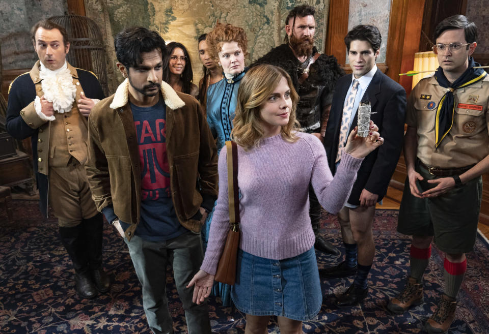 """This image released by CBS shows Utkarsh Ambudkar, foreground left, and Rose McIver in a scene from the comedy series """"Ghosts."""" (Cliff Lipson/CBS via AP)"""