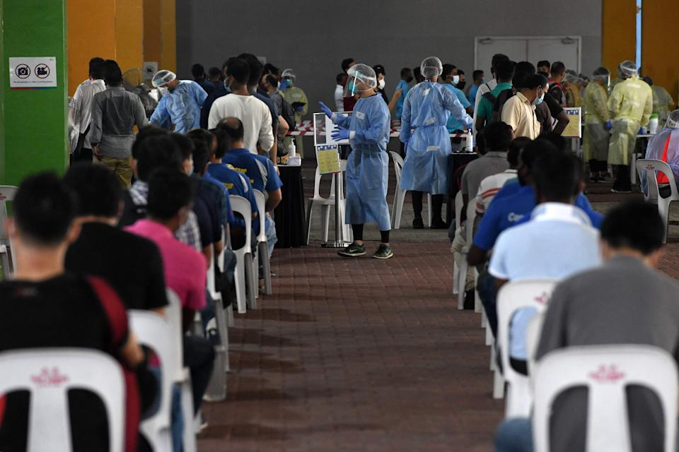 Essential workers wait to take nasal swab tests to detect the COVID-19 novel coronavirus before returning to work in Singapore on June 10, 2020. (Photo by Roslan RAHMAN / AFP) (Photo by ROSLAN RAHMAN/AFP via Getty Images)