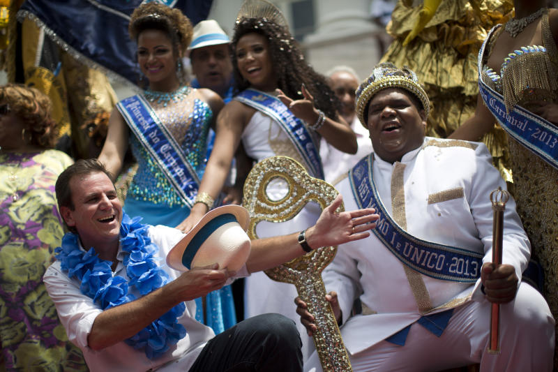 Rio de Janeiro's Mayor Eduardo Paes, left, gestures to the mythical jester figure who reigns over Carnival, this year's King Momo; the crowned and costumed Milton Rodrigues Junior, as he holds the key of the city at the official ceremony kicking off the five day bash, in Rio de Janeiro, Brazil, Friday, Feb. 8, 2013. (AP Photo/Felipe Dana)
