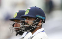 India's captain Virat Kohli, right, and batting partner Cheteshwar Pujara wait to walk into the field after the lunch break during the second day of the World Test Championship final cricket match between New Zealand and India, at the Rose Bowl in Southampton, England, Saturday, June 19, 2021. (AP Photo/Ian Walton)