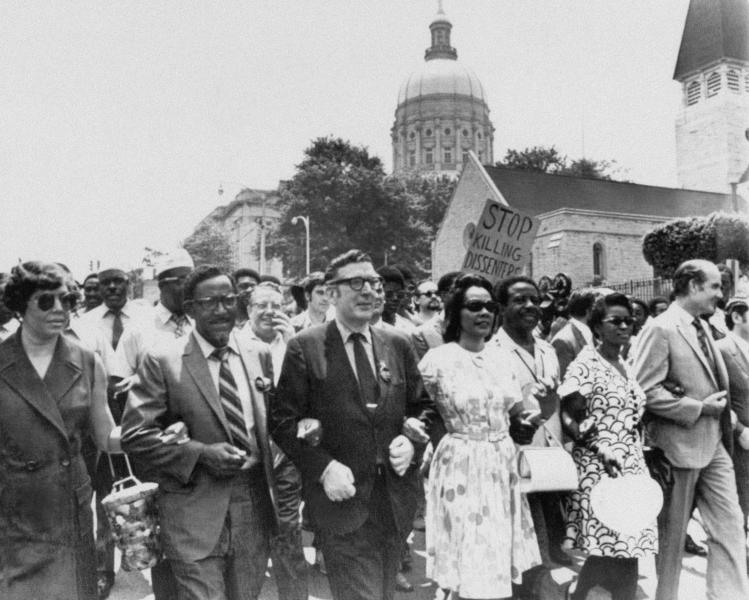 FILE - In this May 1970 file photo, Leonard Woodcock, newly elected president of the United Auto Workers Union, in glasses and dark suit, locks arms with Coretta Scott King, wife of slain the Rev. Dr. Martin Luther King Jr., and the Rev. Joseph E. Lowery as they lead several thousand marchers past the state Capitol in Atlanta in a protest march against war, violence and racial repression. Lowery, a veteran civil rights leader who helped the Rev. Dr. Martin Luther King Jr. found the Southern Christian Leadership Conference and fought against racial discrimination, died Friday, March 27, 2020, a family statement said. He was 98. (AP Photo, File)