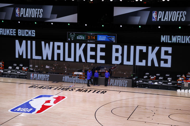Referees stand on an empty court before the start of a scheduled game between the Milwaukee Bucks and the Orlando Magic for Game 5 of an NBA basketball first-round playoff series, Wednesday, Aug. 26, 2020, in Lake Buena Vista, Fla. (Kevin C. Cox/Pool Photo via AP)
