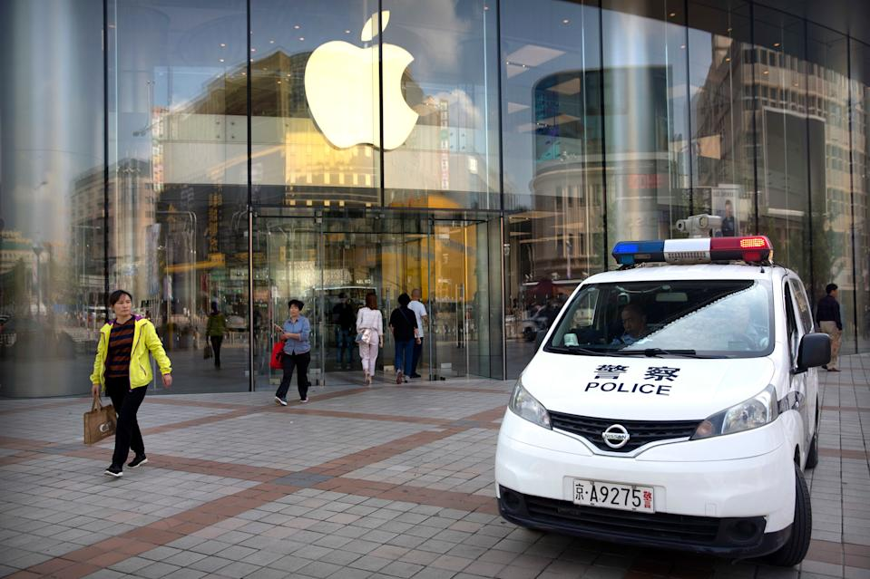 """Chinese police sit in their vehicle as it is parked outside an Apple store at an outdoor shopping area in Beijing, Tuesday, Sept. 25, 2018. A Chinese trade envoy said Tuesday that talks with Washington are impossible while the United States """"holds a knife"""" to Beijing's neck by imposing tariff hikes. (AP Photo/Mark Schiefelbein)"""