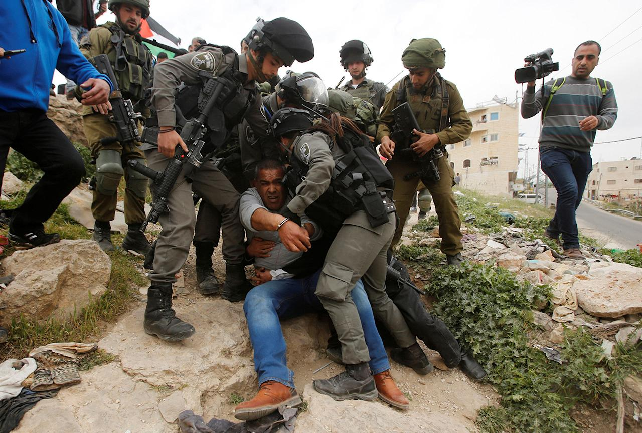<p>Israeli troops detain a Palestinian demonstrator during a protest marking Land Day in the West Bank city of Hebron, March 30, 2017. (Mussa Qawasma/Reuters) </p>