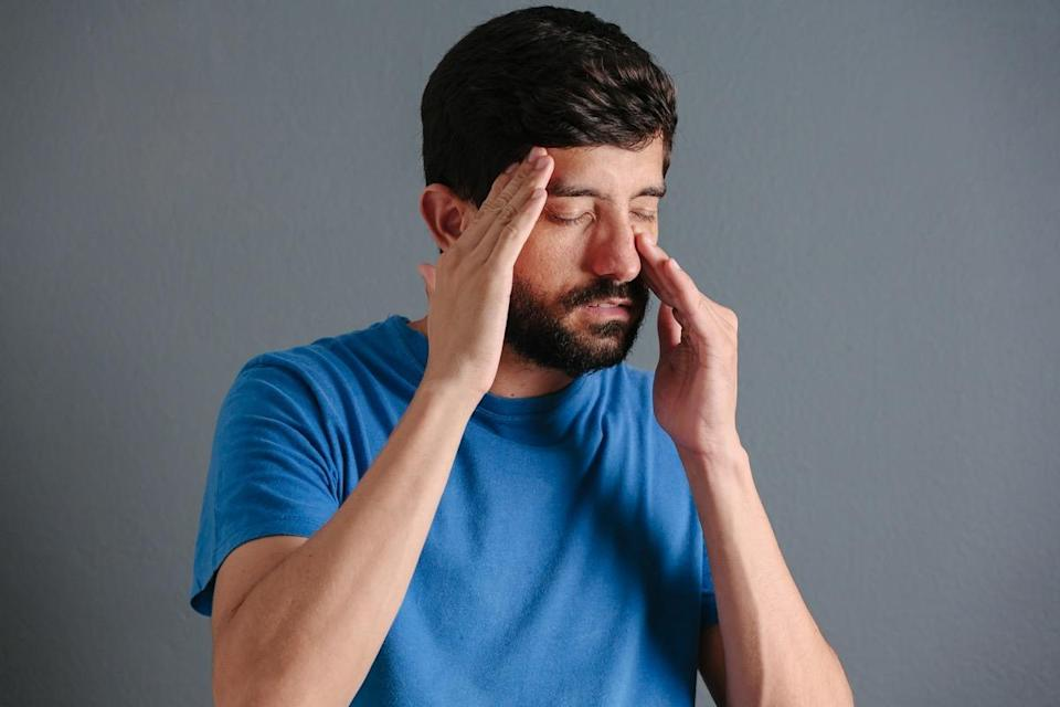 man holding his nose because sinus pain