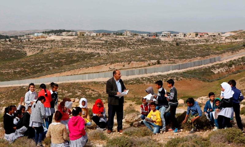 A Palestinian teacher gives a lesson in front of a cement wall separating them from an Israeli settlement in the West Bank