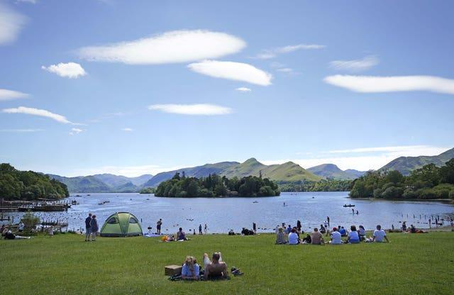 People enjoy the weather at Derwentwater in the Lake District National Park near Keswick