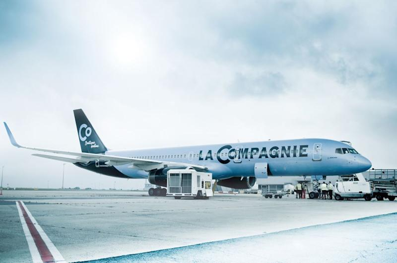 A La Compagnie plane parked on the tarmac, surrounded by baggage-handling equipment