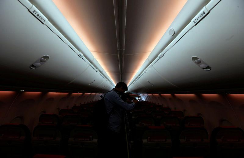FILE PHOTO: A man takes pictures inside a Norwegian Air Boeing 737-800 during the presentation of Norwegian Air first low cost transatlantic flight service from Argentina at Ezeiza airport in Buenos Aires