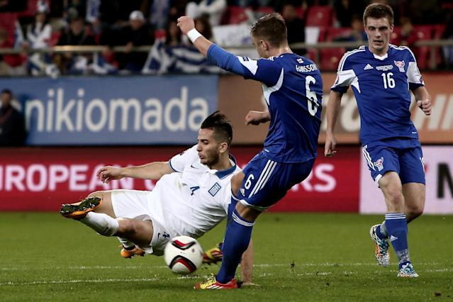 Greece's defender Kostas Manolas (L) vies for the ball with Faroe Island's midfielder Hallur Hansson (C) during their Euro 2016 qualifier in Piraeus, near Athens, on November 14, 2014 (AFP Photo/Angelos Tzortzinis)
